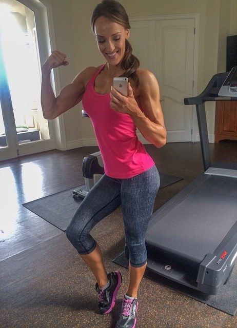 Heidi Carlsen flexing her biceps as she takes a selfie besides a treadmill machine