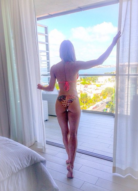 Heidi Carlsen standing on her toes on a balcony, looking at a sunny and beautiful scenery in front of her, and showing her awesome legs and glutes