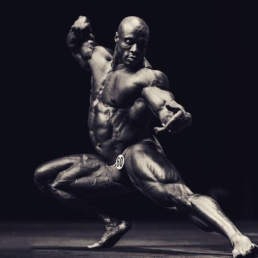 Jeff Beckham posing on a bodybuilding stage crouched down in an artistic fashion