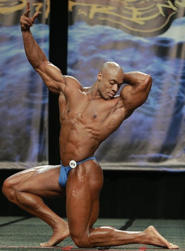 Jeff Beckham posing on a bodybuilding stage kneeling down opening his chest towards the crowd