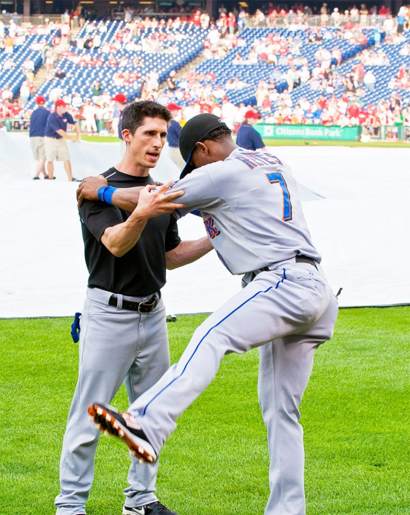Jeff Cavaliere working as the head physical therapist for New York Mets with Jose Reyes on the field