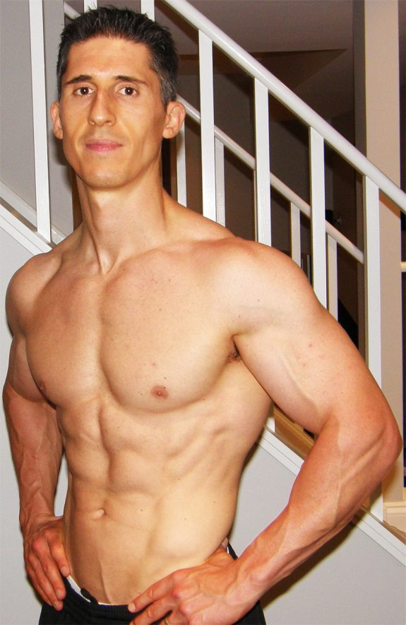 Jeff Cavaliere posing in his house, showing his shredded physique as an online fitness coach called athlean x