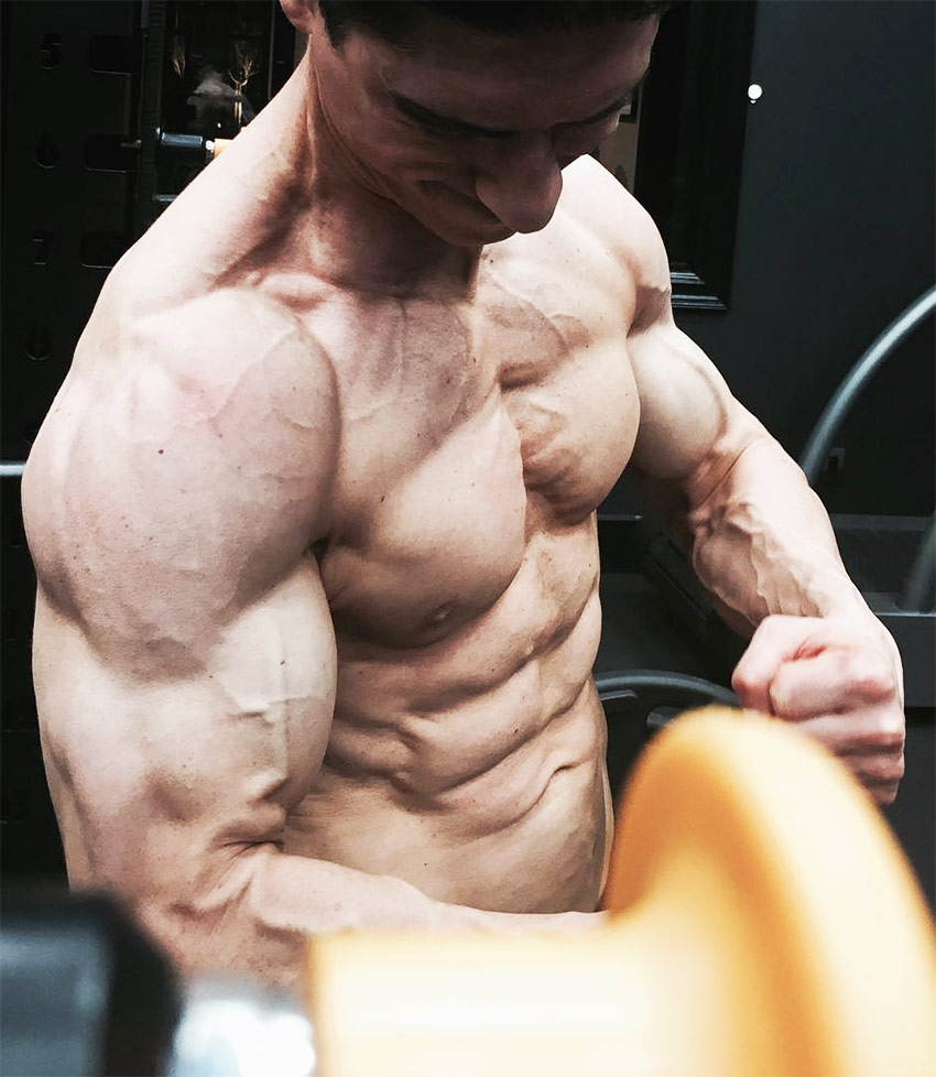 Jeff Cavaliere showing how shredded he is by tensing his arms, abs and chest while posing for a photo.