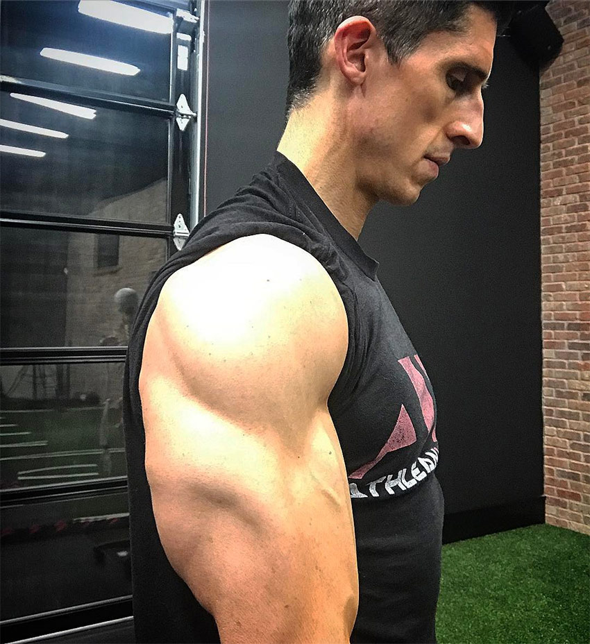 Jeff Cavaliere taking a photo on a side-view so you can see his triceps and size of his biceps, displaying his shredded arms and physique.