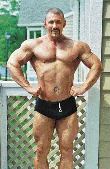 Jerry Ward in black shorts, in a front lat spred pose, showing his ripped body