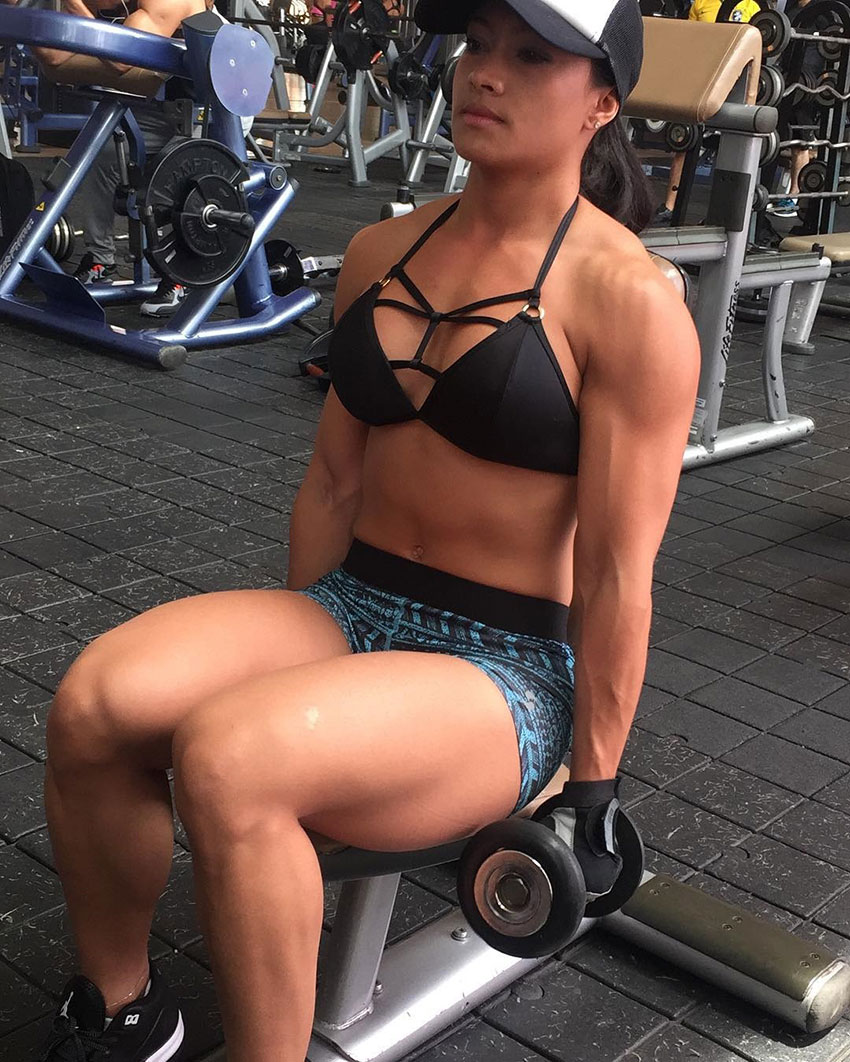 Jessica Olaya in the gym sitting down performing bicep curls