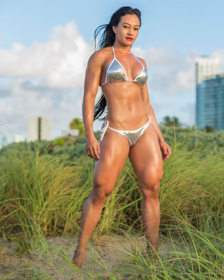 Jessica Olaya standing in a field wearing a bikini looking strong and pipped