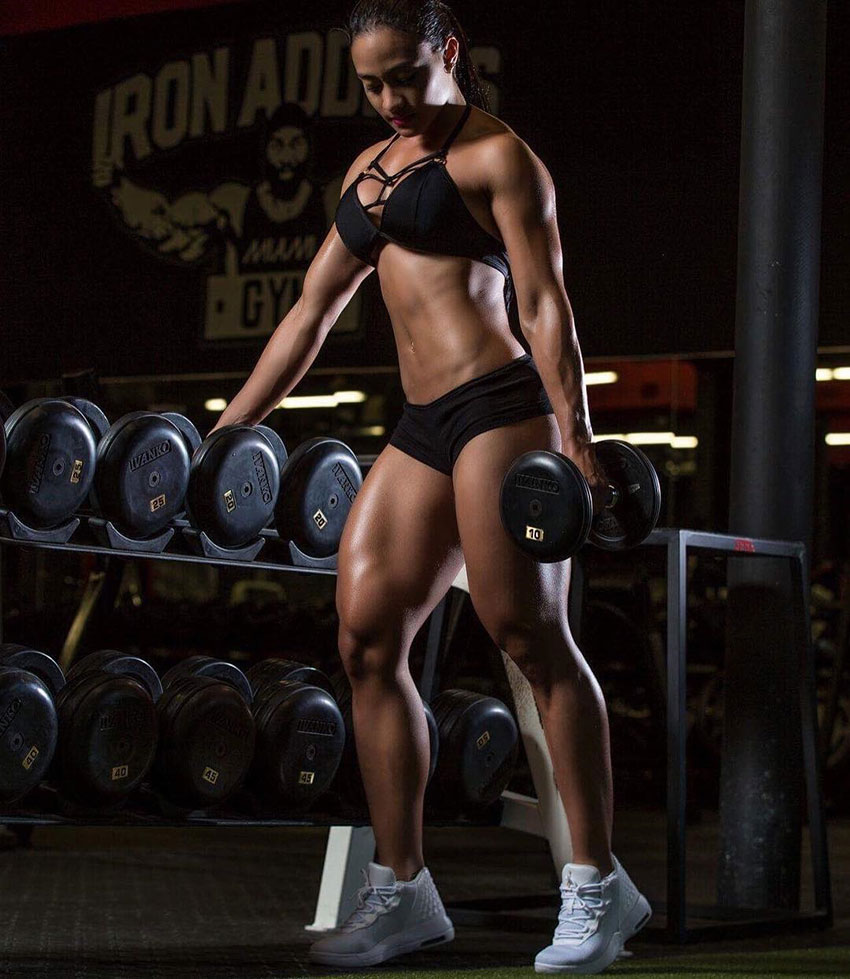 Jessica Olaya in the gym taking weights from a weight rack