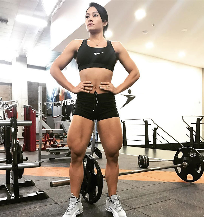 Jessica Olaya standing in teh gym with her hands on her hips showing her large lega muscles