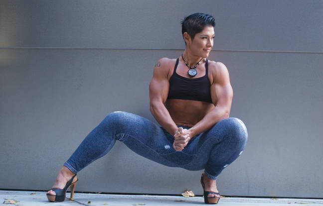 Kortney Olson Crouching down tensing her biceps and wearing jeans