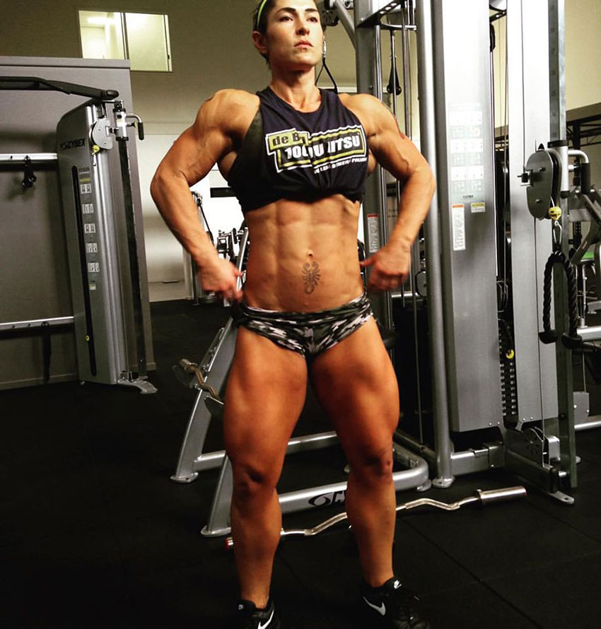 Kortney Olson standing in the gym wearing short shorts, and a short top flexing and posing like a bodybuilding