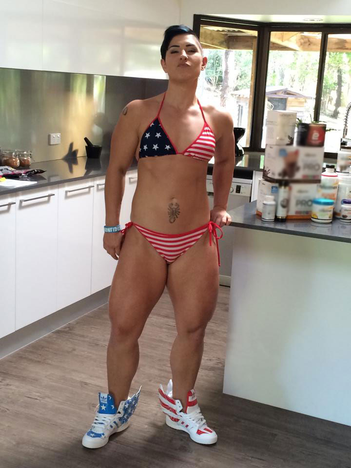 Kortney Olson standing in the kitchen looking bulky with large muscles while wearing an American flag bikini