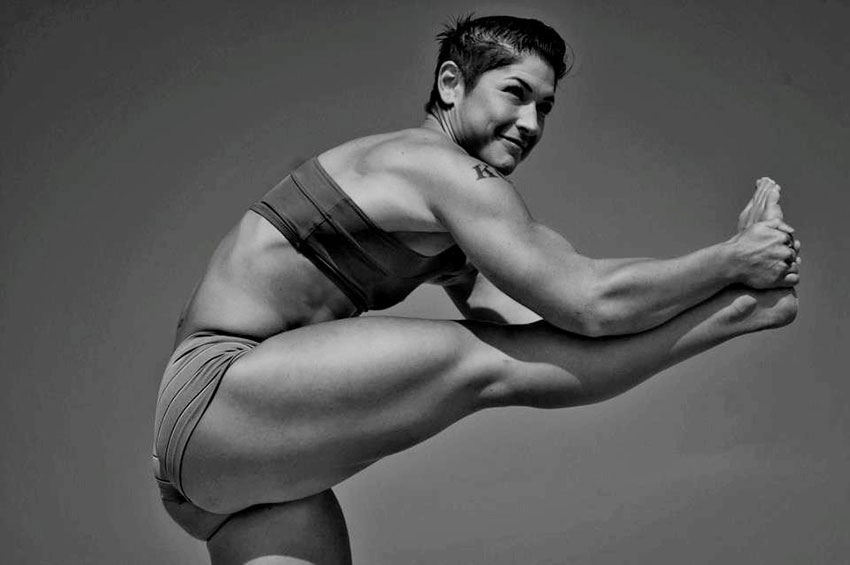 Kortney Olson standing on one leg while stretching her other leg showing her large leg muscles and muscular body