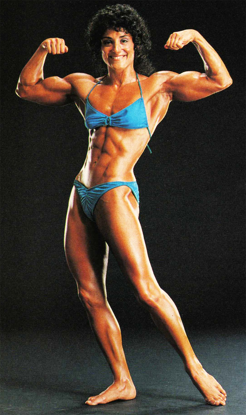 Profile picture of Laura Combes posing in her stage bikini, flexing her biceps and displaying her trademark figure.