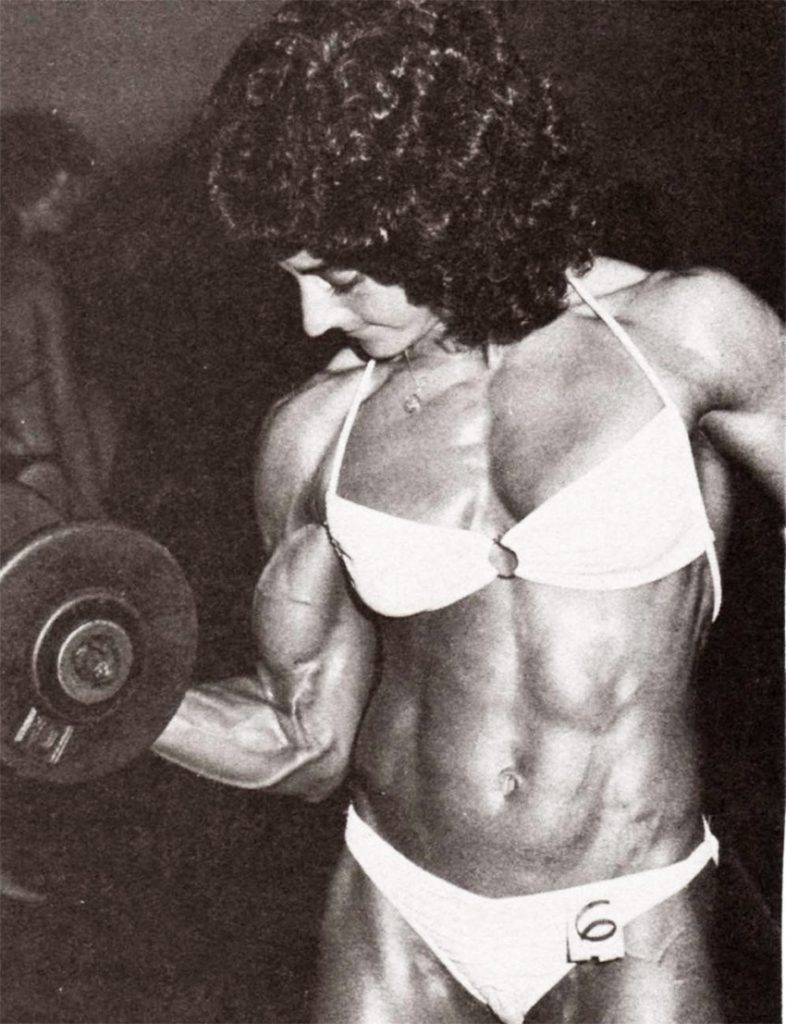 Laura Combes training her arms in the gym, lifting weights and displaying her muscular definition.