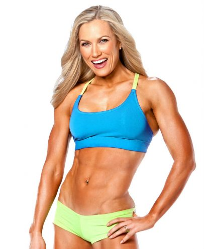 Lindy Olsen standing with her hand on her hip displaying her ripped abs