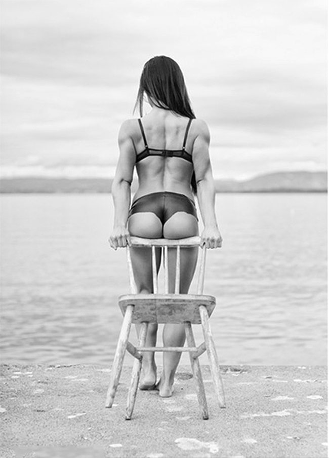 Lone-Noras-displaying-her-legs-and-glutes-on-a-chair-on-the-beachfront.
