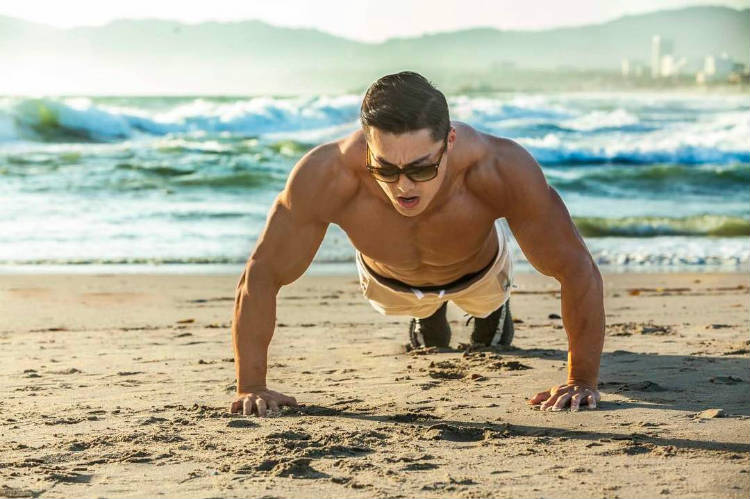 Long Wu completing a press-up on the beach
