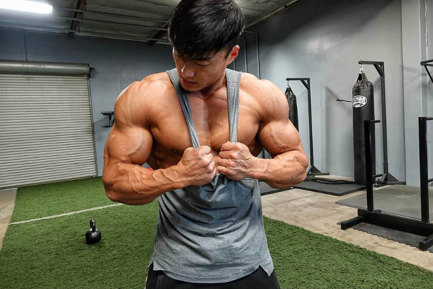 Long Wu tensing his biceps in a gym