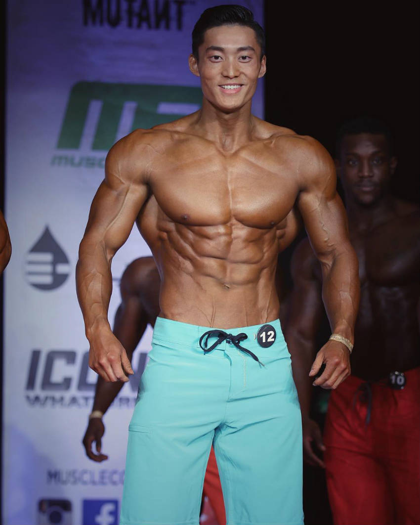 Long Wu standing in blue shorts at a physique competition