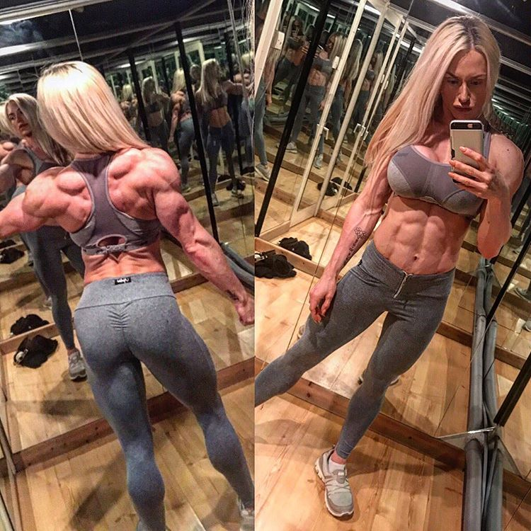 Louise Rogers taking a selfie in the mirror, as she shows her legs and glutes in grey leggings, and also her awesome abs and back
