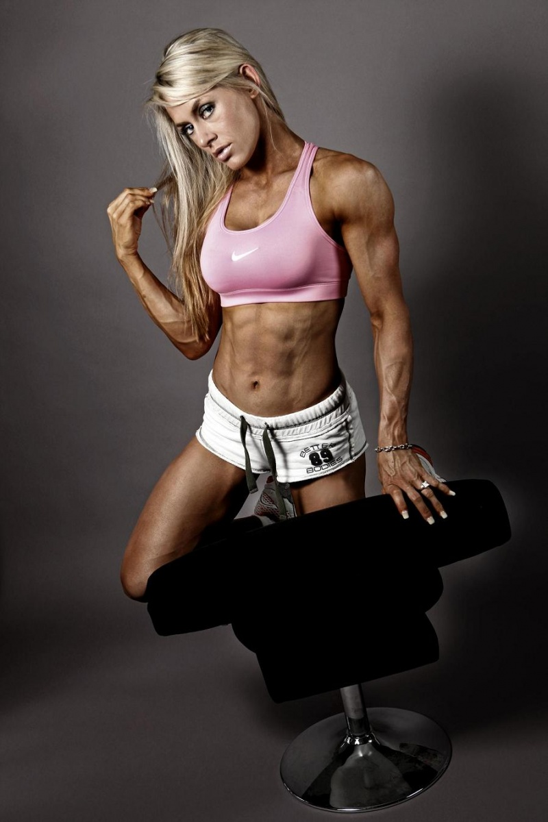 Louise Rogers kneeling on some sort of a black chair, while doing photo shoot, showing her ripped abs, aesthetic and vascular arms, and awesome legs