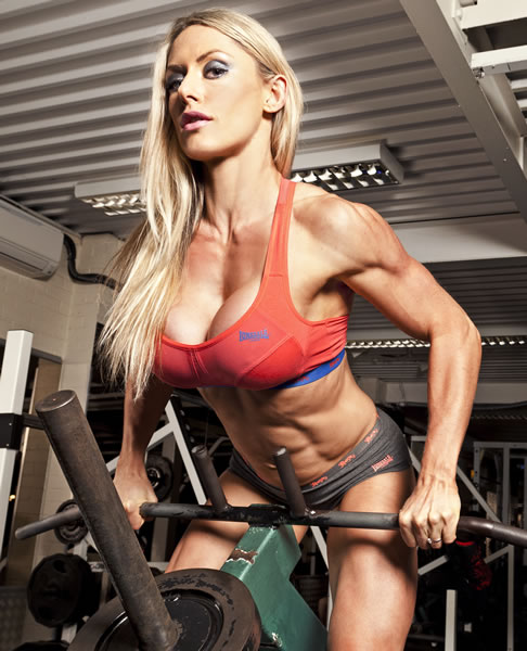 Louise Rogers doing machine bent over rows in the gym, as she shows her ripped physique