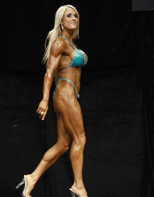 Louise Rogers walking onto a stage, as she smiles to the audience and judges, showing her awesome conditioning