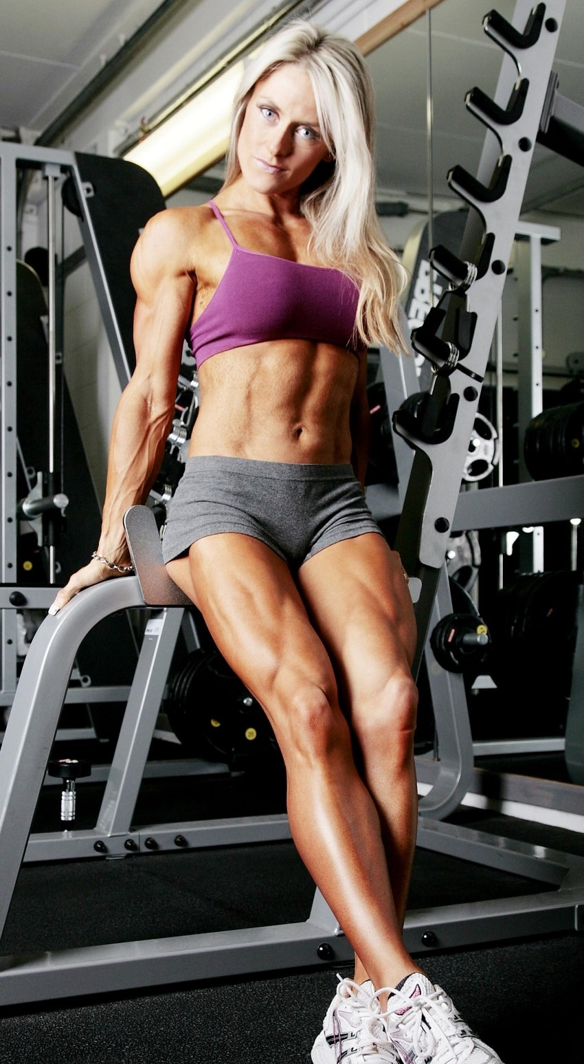 Louise Rogers sitting on a machine in gym, as she shows her lean legs, abs, and arms