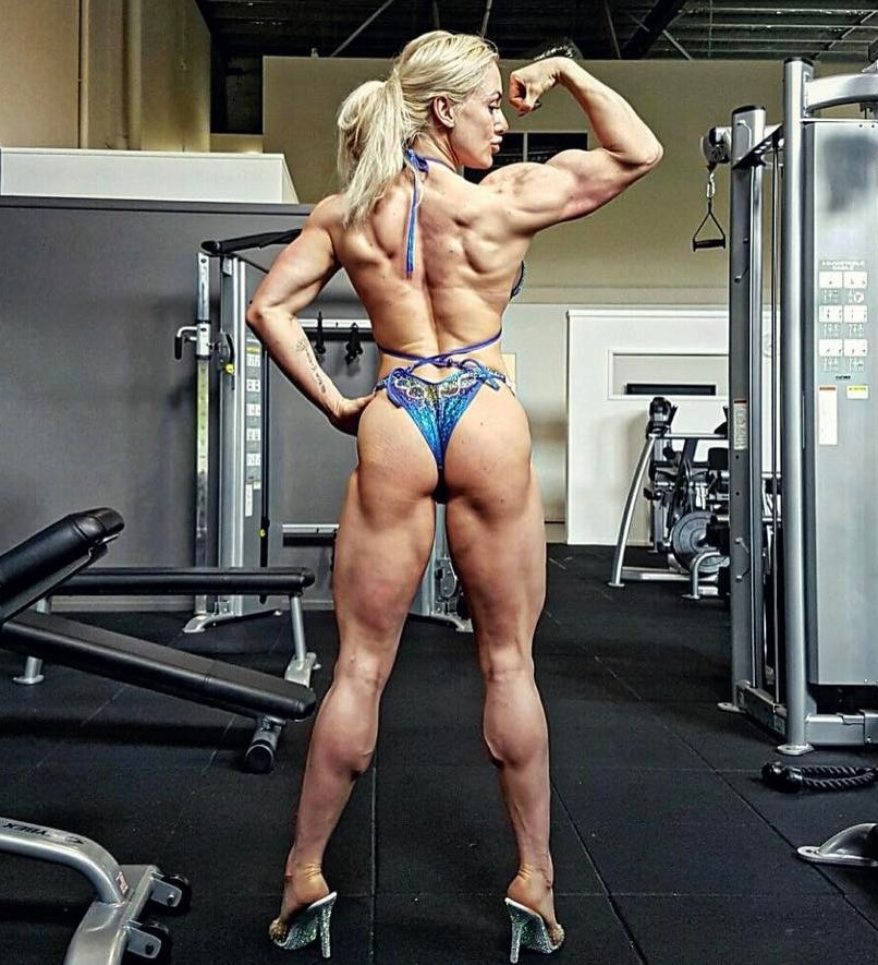 Louise Rogers in a bikini, showing her ripped physique from the back as she flexes one of her arms