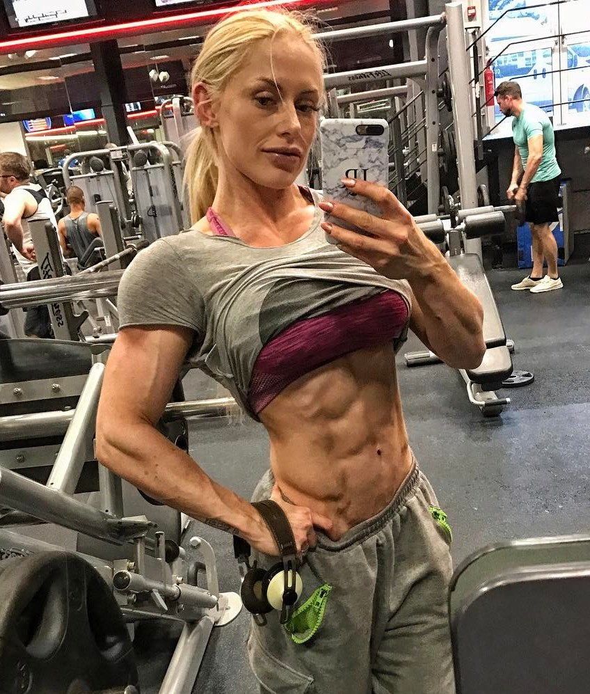 Louise Rogers taking a selfie in the gym mirror, showing her ripped abs and arms