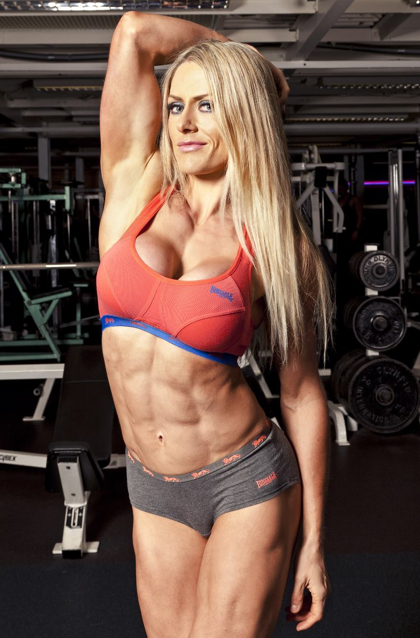 Louise Rogers with one of her arms in her long blond hair, showing her chest, lats, abs, and legs