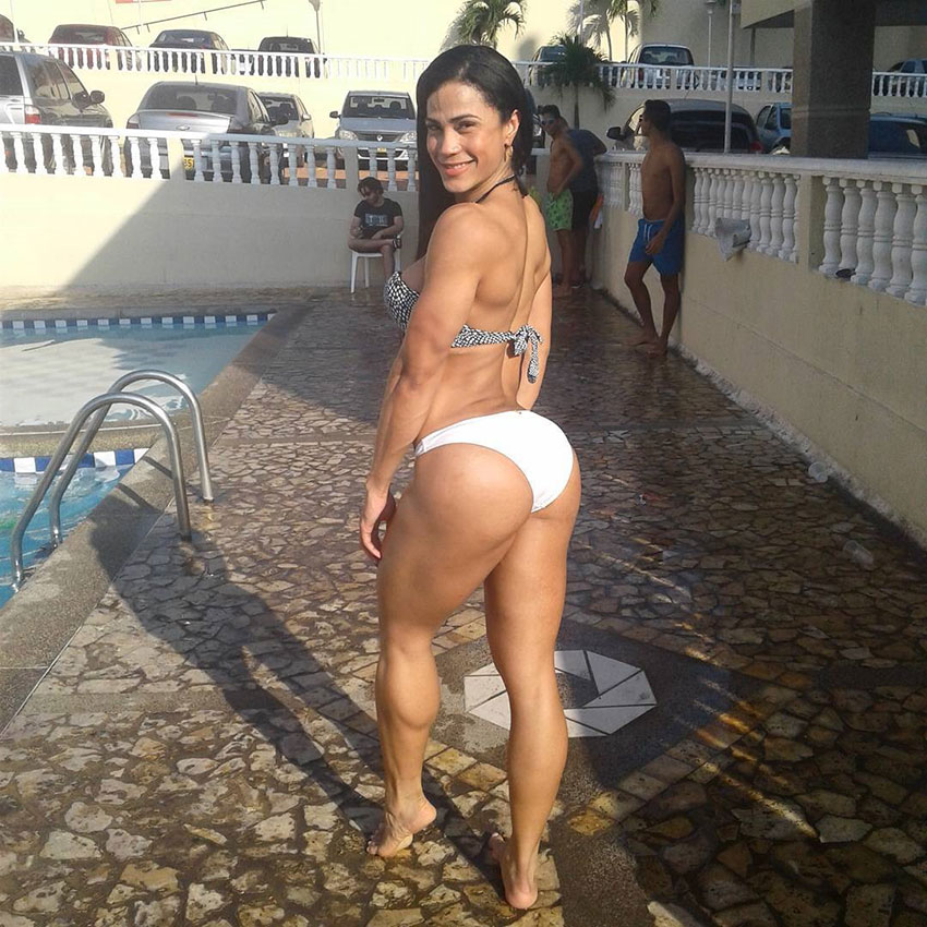 Luz Elena Echeverria Molina flexing her glutes standing next to a swimming pool wearing a white bikini