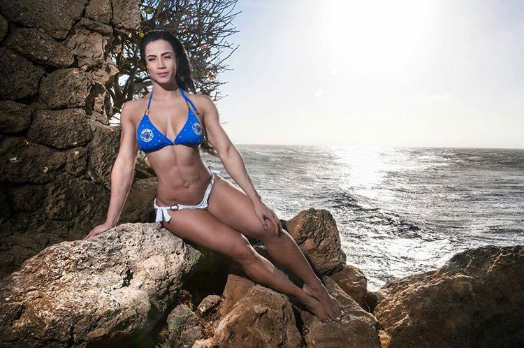 Luz Elena Echeverria Molina sitting on a rock next to the ocean wearing a bikini looking strong and healthy