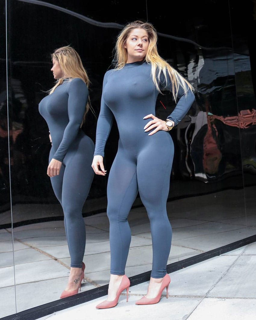 Mia Sand profile picture, standing next to a wall mirror wearing a full body training suite