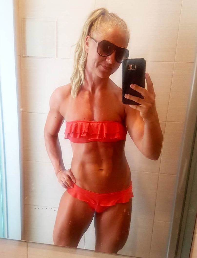 Michaela Augustsson taking a selfie in a red swimsuit, flexing her ripped abs, and aesthetic arms