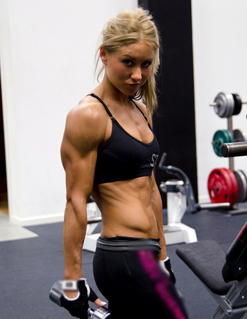 Michaela Augustsson stretching in the gym, while at the same time flexing her triceps, and showing her lean obliques and abs
