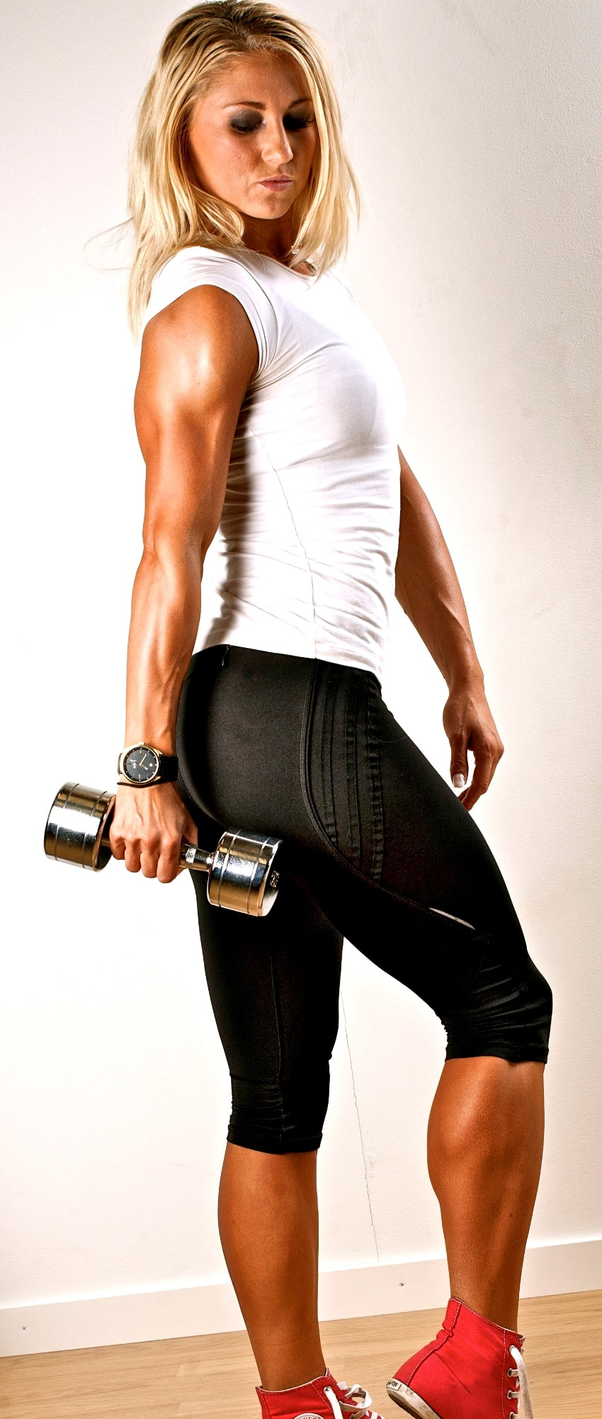 Michaela Augustsson during a phtooshoot, holding a light dumbbell in her hand while displaying her calves and arms from the side