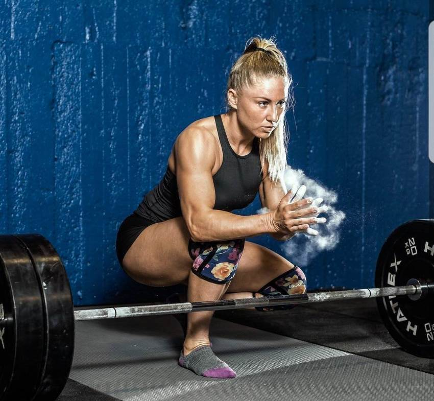 Michaela Augustsson in a squatting position without shoes, preparing to do a deadlift