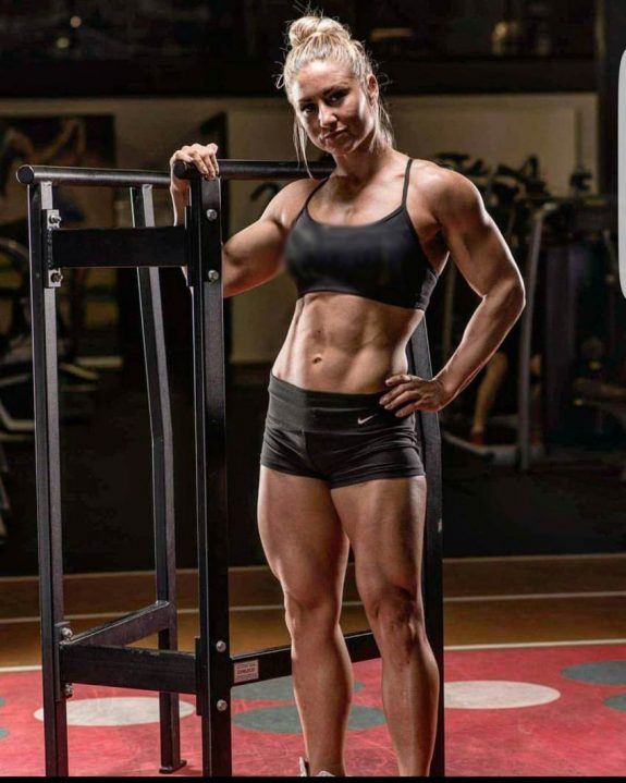 Michaela Augustsson standing on a track, while being in a revealing sportswear, showing her lean abs, legs, and arms from the front