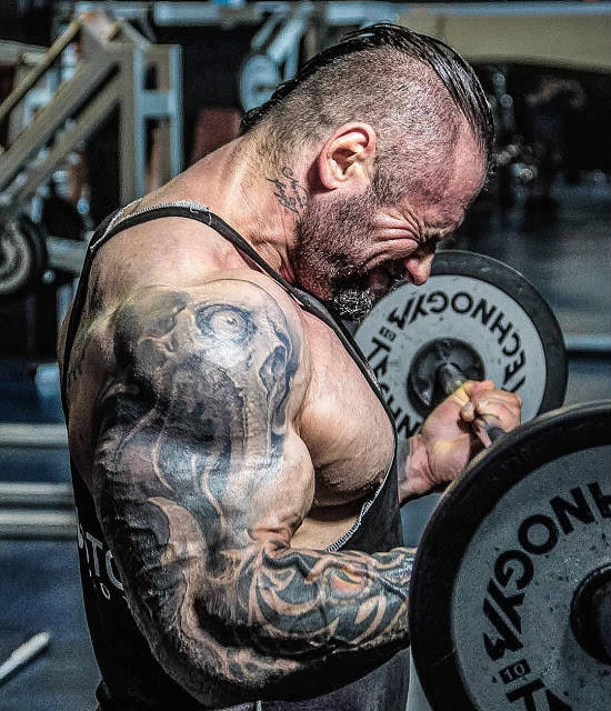 Miha Zupan completing a bicep barbell curl