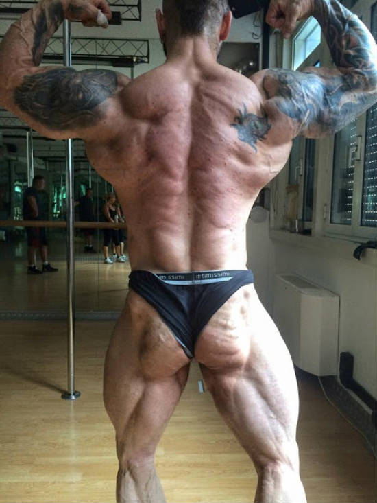 Miha Zupan flexing his back muscles in the gym