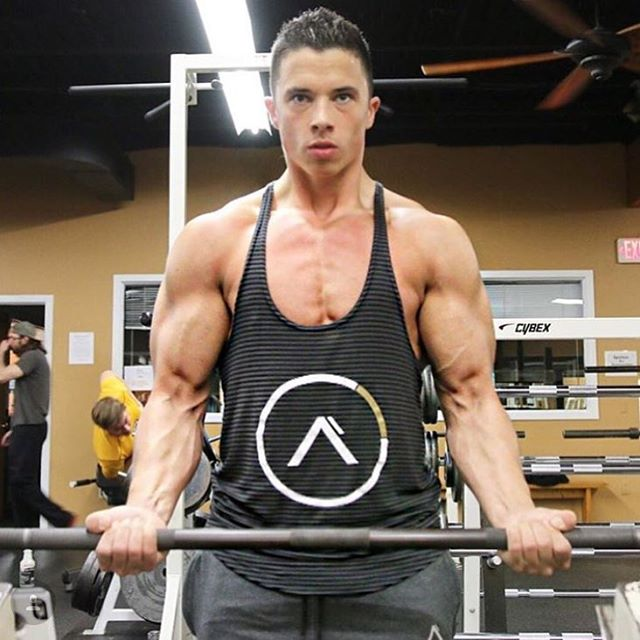 Nick Wright in a black tank top, doing barbell biceps curls in the gym