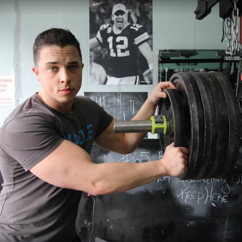 Nick Whright putting a lot of weight on a weight bar, preparing to do a heavy lift, as she looks straight into the camera, and flexes his arms