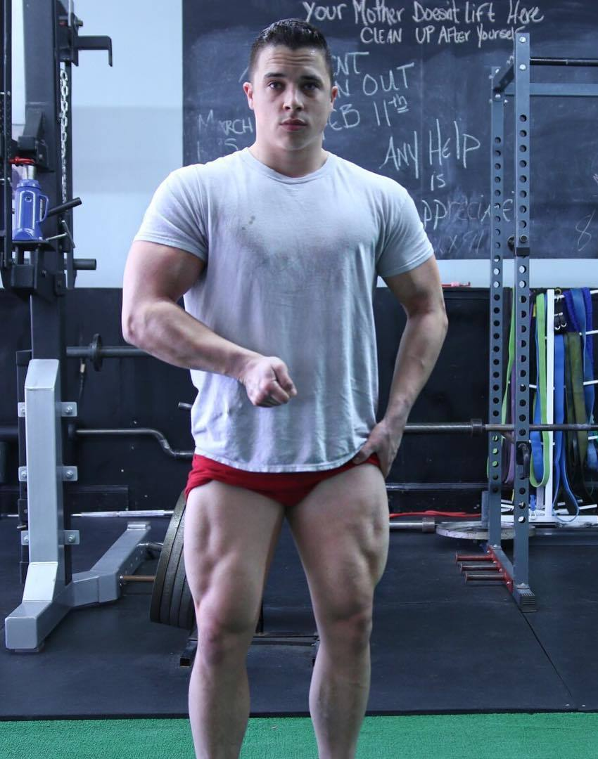 Nick Wright flexing his arm and his legs in the gym, while being in red shorts and white t-shirt