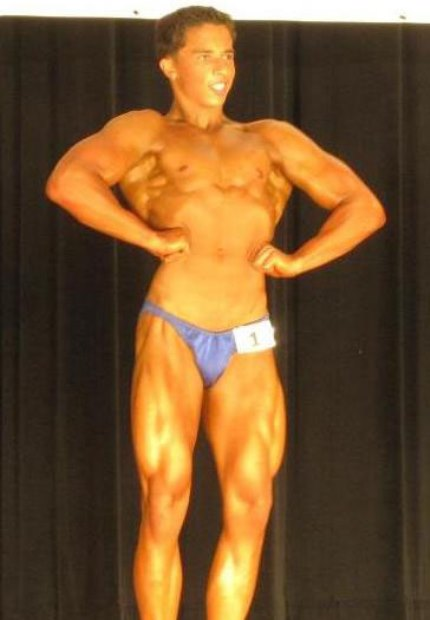 Nick Wright in a front lat spread pose on the stage