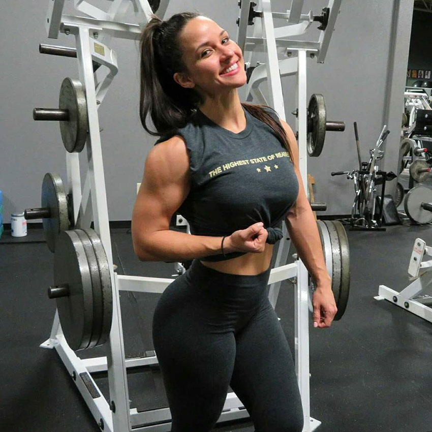 Renee Enos standing in the gym flexing her right bicep smiling looking happy