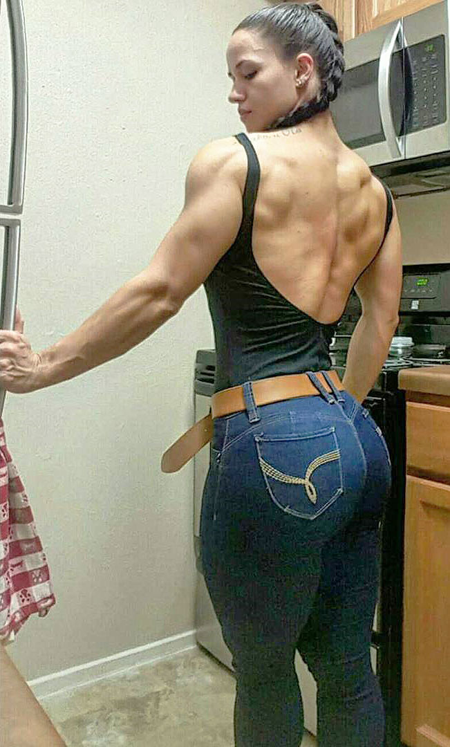 Renee Enos standing in the kitchen flexing her big and strong back wearing a backless t-shirt