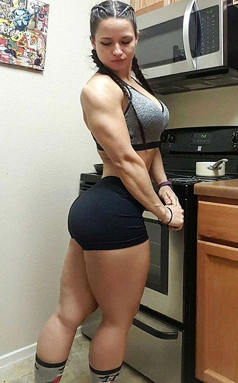Renee Enosstanding in the kitchen with short shorts on, flexing her glutes and legs