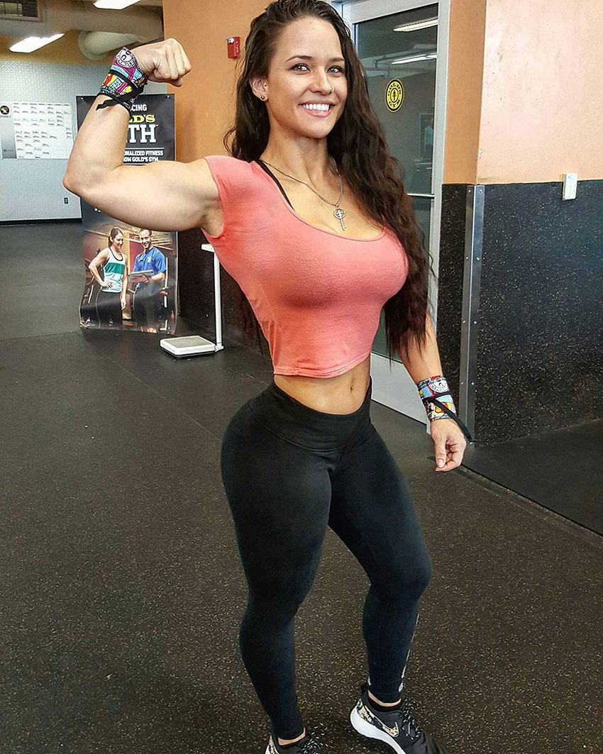 Renee Enos standing in the gym in a pink t-shirt flexing her right bicep